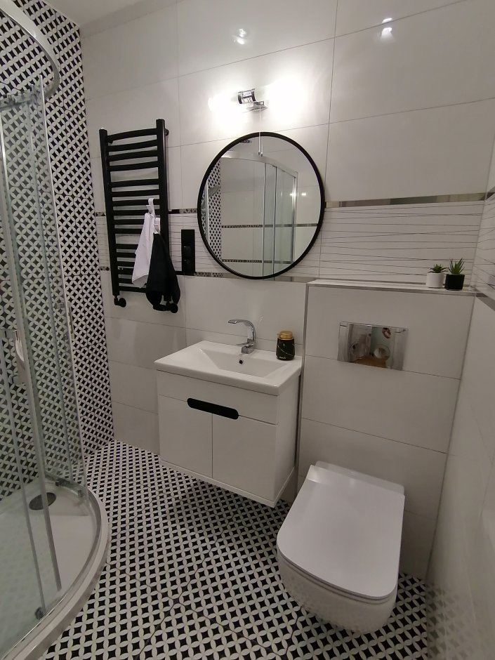 Łazienka w czerni i bieli z mocnymi czarnymi akcentami - np. grzejnikiem