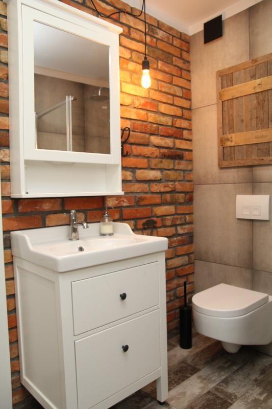 Białe meble na tle ceglanej ściany - aranzacja łazienki rustykalnej