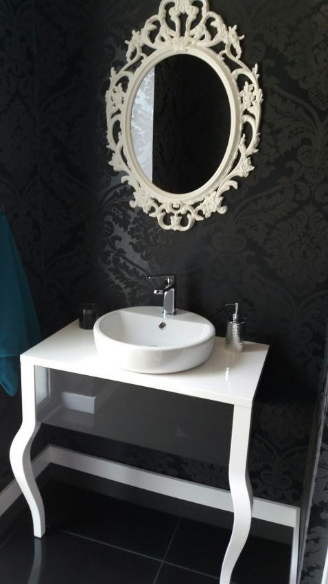 Biała konsola z umywalką nablatową i fantazyjne lustro na tle czarnej ściany