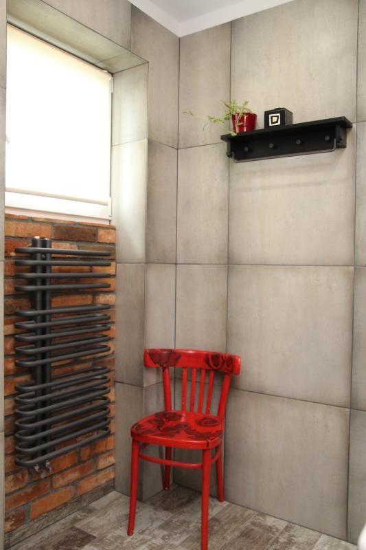 Płytki wielkoformatowe imitujące beton oraz postarzane krzesło w łazience rustykalnej