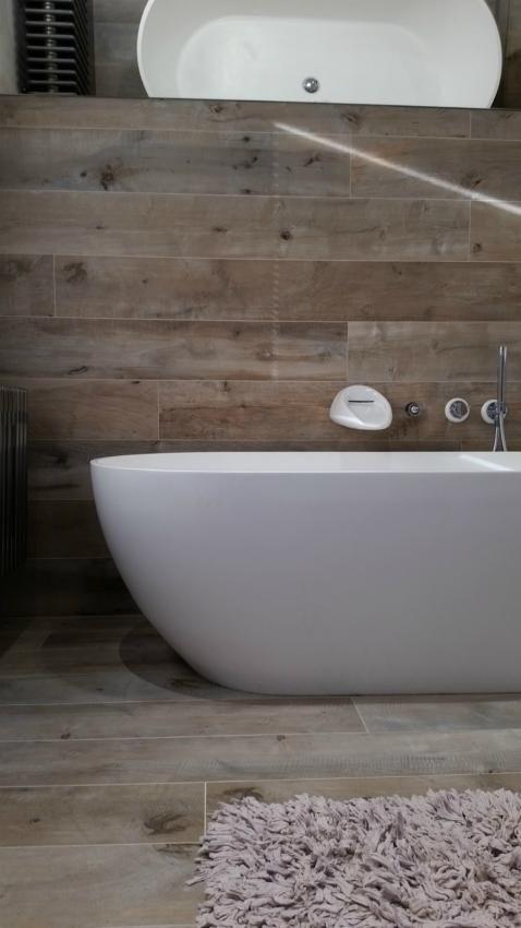 Lustro na skośnej ścianie nad wanną w łazience na poddaszu