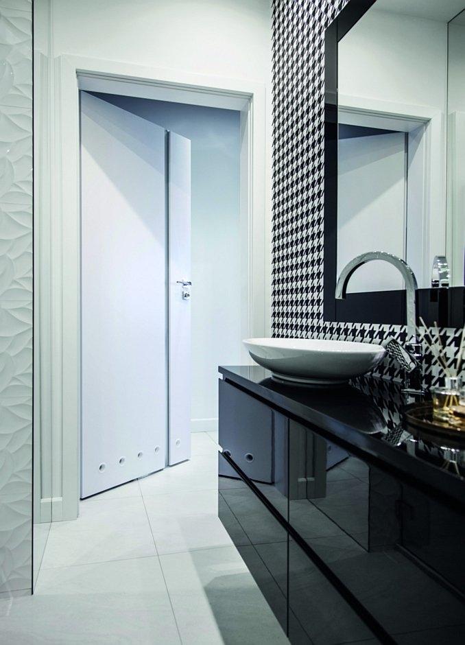 Białe drzwi i wzór pepitka w małej łazience