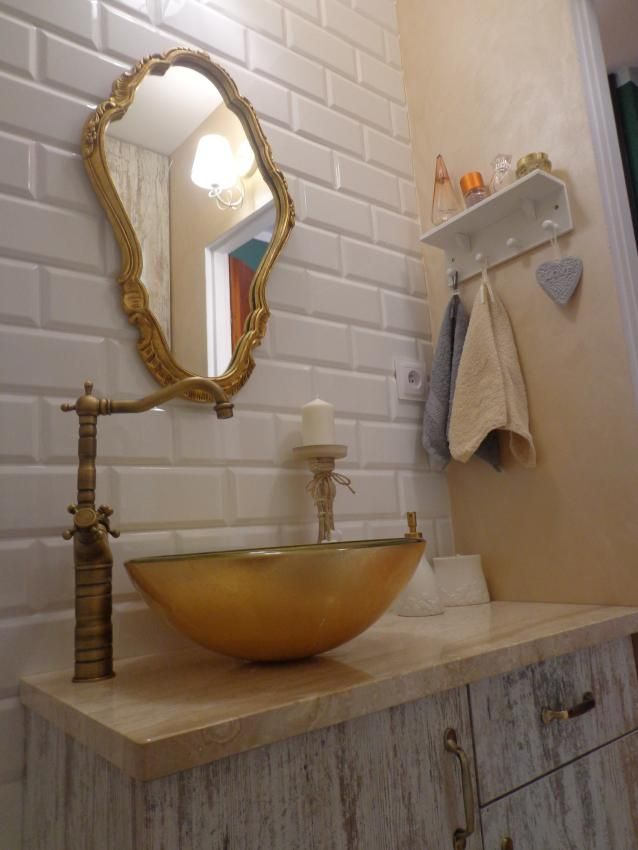 Łazienka w stylu retro z białymi kafelkami i dodatkami w kolorze złota