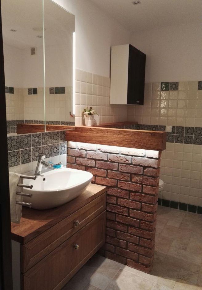 Drewniana szafka pod umywalkę oraz ceglany murek w łazience w stylu rustykalnym