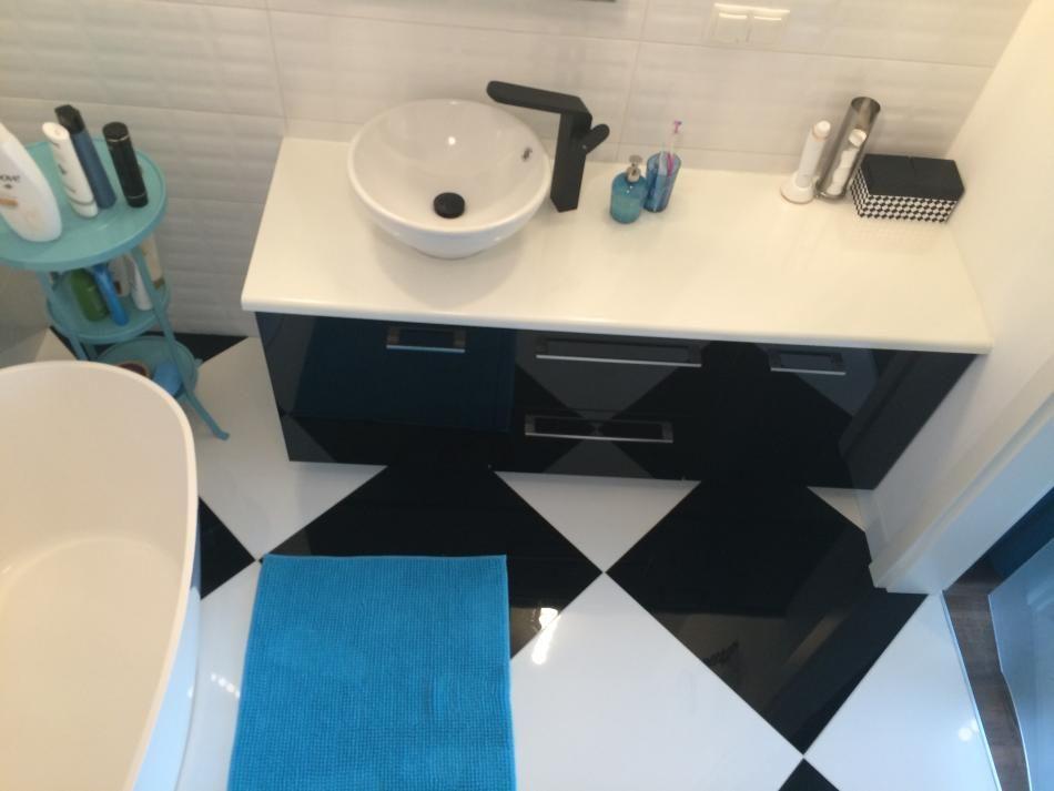 Biało-czarna aranżacja łazienki z dodatkami w niebieskim kolorze